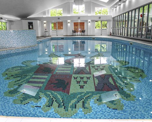 Large indoor swimming pool with outside view.