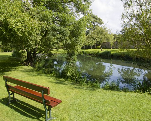 A well maintained lawn with a waterfront and a picnic seat.