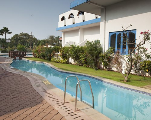 An outdoor swimming pool alongside resort units.