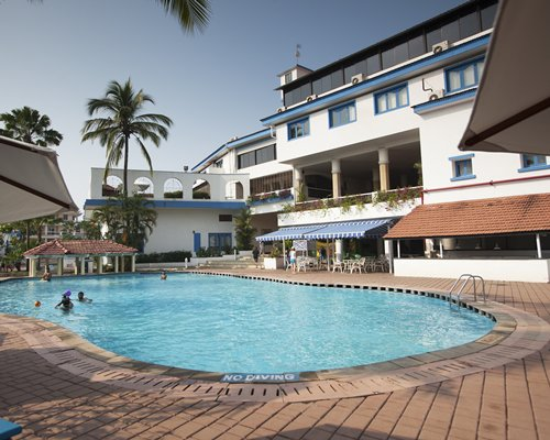 An outdoor swimming pool alongside the multi story resort.