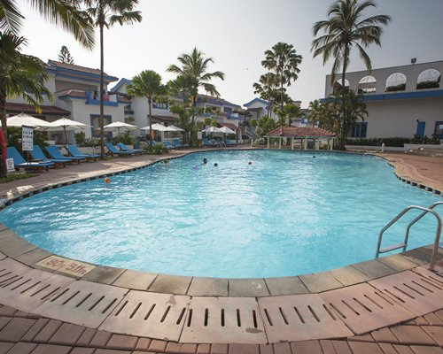 An outdoor swimming pool with chaise lounge chairs and sunshades alongside resort.