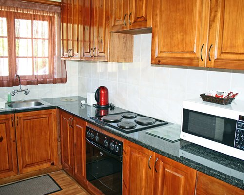 A well equipped kitchen with outside view.