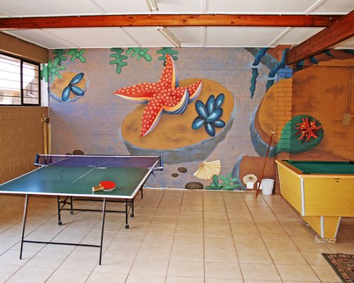 Outdoor recreation room with ping pong and pool table.