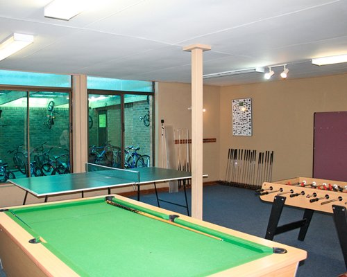 An indoor recreational room with a pool table foosball table and ping pong.