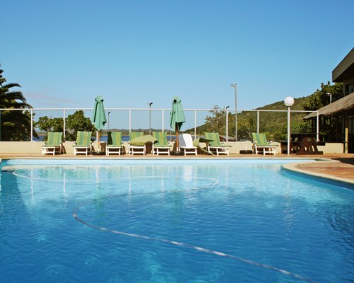 An outdoor swimming pool with chaise lounge chairs and sunshades alongside resort units.