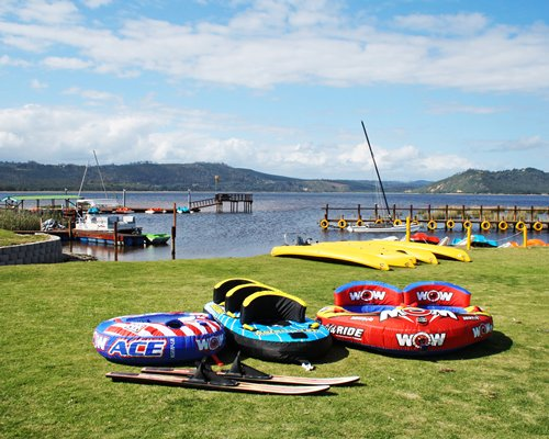 Exterior view of a wooden pier boats and inflatable water floats .