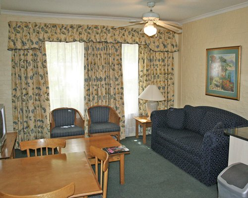 A well furnished living room with a television pull out sofa and dining table.