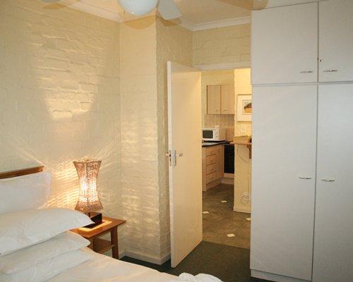 A well furnished bedroom alongside kitchen.