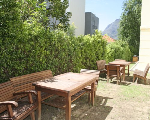 Outdoor picnic area with wooden chairs.