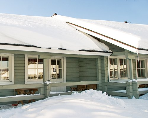 An exterior view of the Holiday Club Yllas 3 covered in snow.