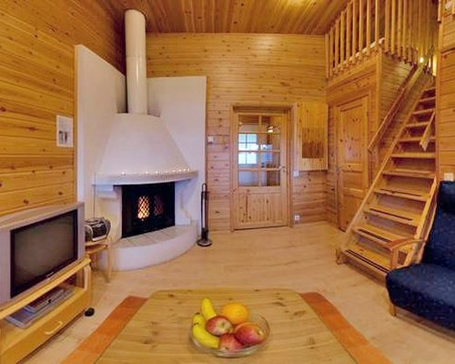 A well furnished living room with television fire in the fireplace and staircase.