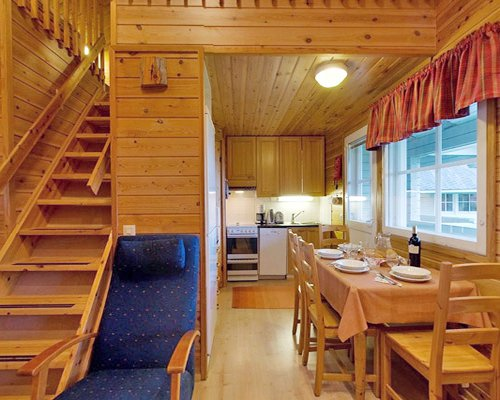 An open plan kitchen with dining area living room wooden stairway and outside view.