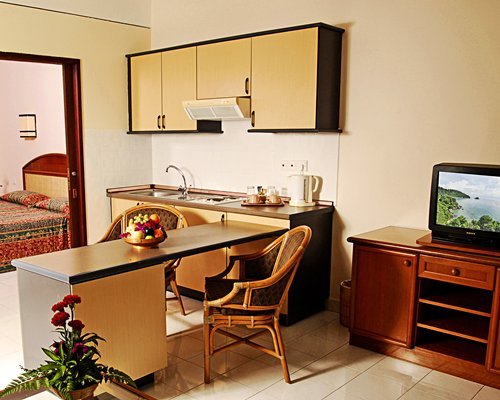 A kitchen with a breakfast bar and television.