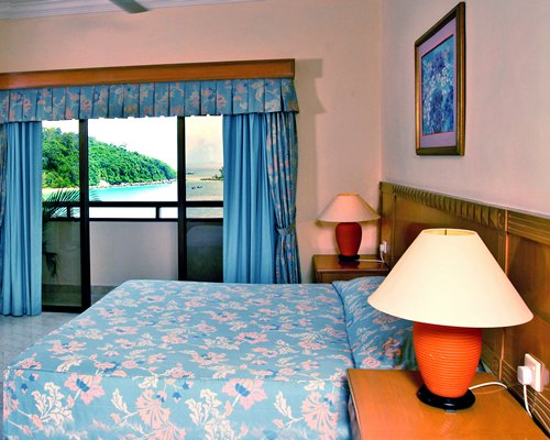 A well furnished bedroom with queen bed balcony and beach view.