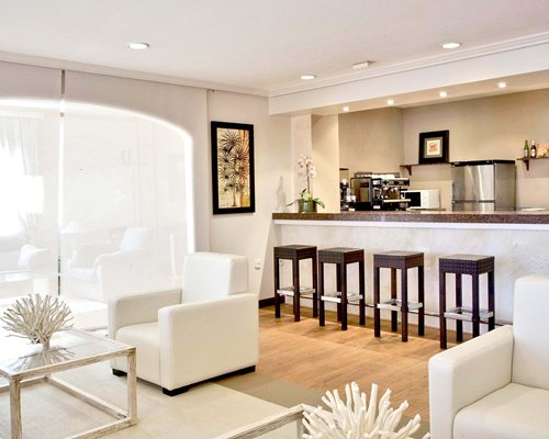 A well furnished living room with open plan kitchen breakfast bar and outside view.