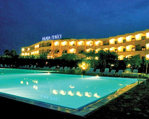 An outdoor swimming pool with chaise lounge chairs alongside Araba Fenice Village resort at night.