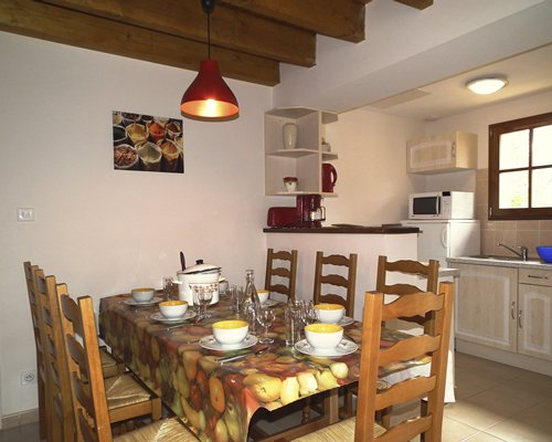 A furnished dining room and a kitchen area.