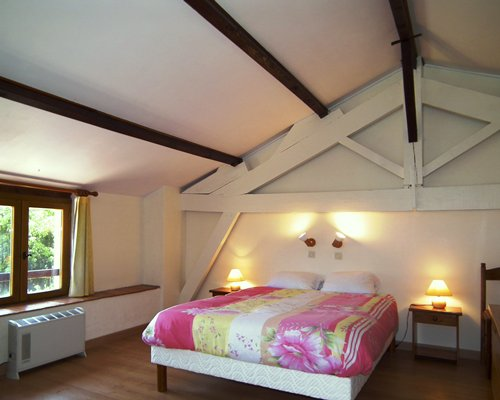 A furnished bedroom with a king bed and outdoor view.