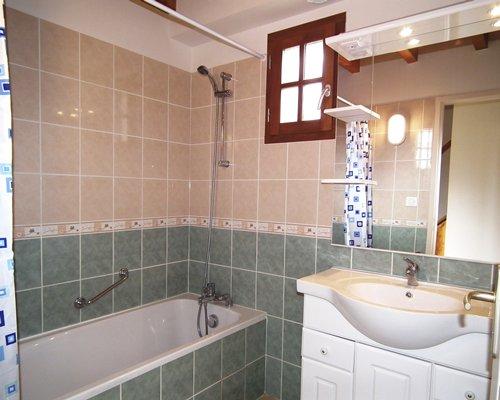 A bathroom with single sink vanity and a bathtub.