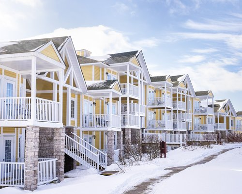 Exterior view of multiple unit balconies with stairway alongside a pathway covered with snow.