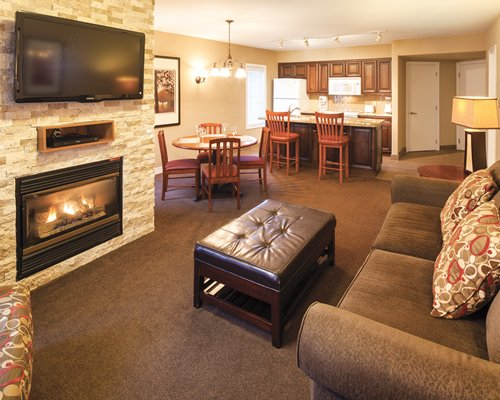 An open plan living and dining area with a television fireplace and a breakfast bar.