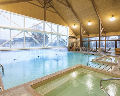 A view of indoor swimming pool and hot tub with chaise lounge chairs and an outside view.