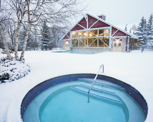 An outdoor hot tub alongside the resort covered in snow.