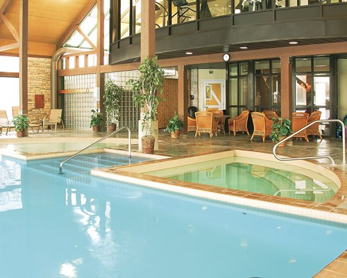 Indoor swimming pool with a hot tub alongside lounge area.