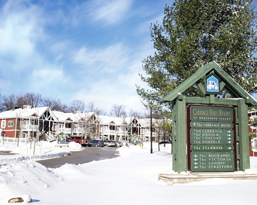 Signboard of Carriage Hills Resort alongside the resort units covered in snow.