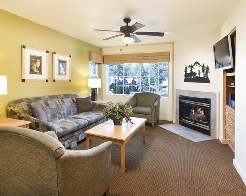 A well furnished living room with television fireplace and an outside view.
