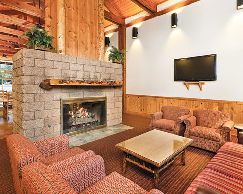 A well furnished living room with a television and a fire in the fireplace.