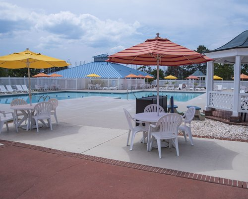 An outdoor swimming pool with chaise lounge chairs patio tables and sunshades.
