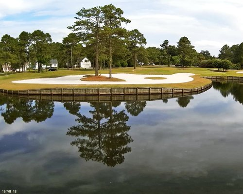 A view of the water surrounded by a golf course.