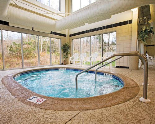 An indoor hot tub with patio furniture and an outside view.