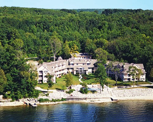 Exterior view of Westwood Shores Resort alongside a lake surrounded by wooded area.