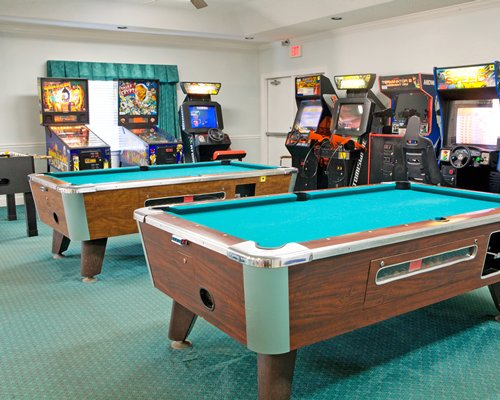 Indoor recreation room with arcade games and pool tables.