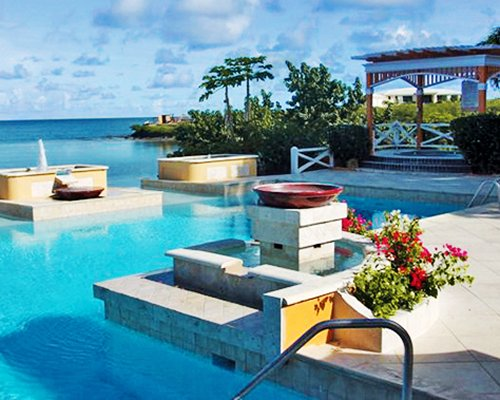 Outdoor swimming pool with hot tub alongside the ocean.
