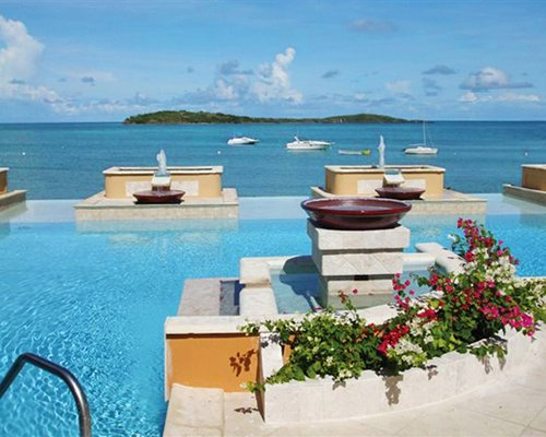 An outdoor swimming pool with water fountain and flowering shrubs alongside the sea.