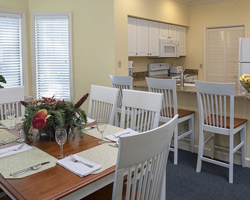 A well furnished dining area alongside kitchen with a breakfast bar.