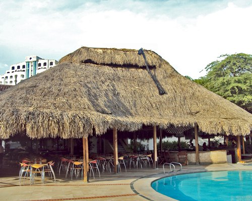Thatched covered outdoor restaurant alongside outdoor pool.