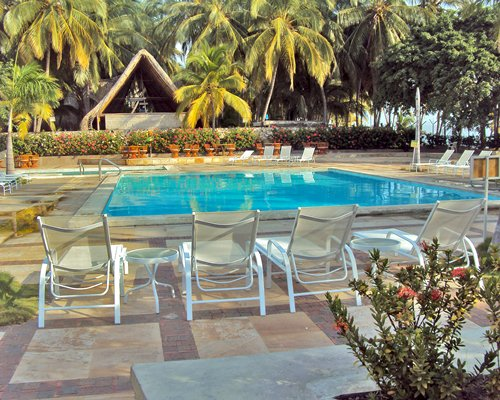 An outdoor swimming pool with chaise lounge chairs surrounded by trees.