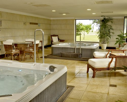 View of indoor hot tub with patio furniture and chaise lounge chairs.