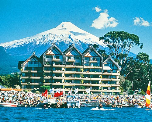 Scenic exterior view of Pucon with multiple balconies alongside the beach and mountains.