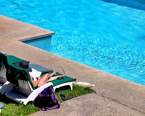 A woman in chaise lounge chair alongside the swimming pool.