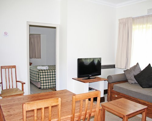 A well furnished living room with television dining area and bedroom with king bed.