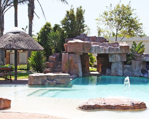 Outdoor grotto pool with fountain and picnic area.