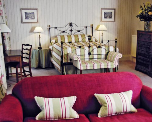 A well furnished bedroom with love seat and dining area.