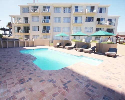 An outdoor swimming pool with chaise lounge chairs and sunshades alongside multi story units.