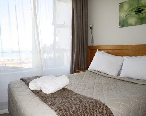 A well furnished bedroom with beach view.