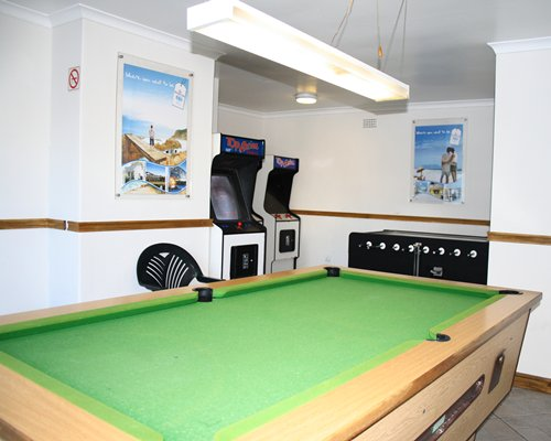 An indoor recreation room with a pool table and arcade games.